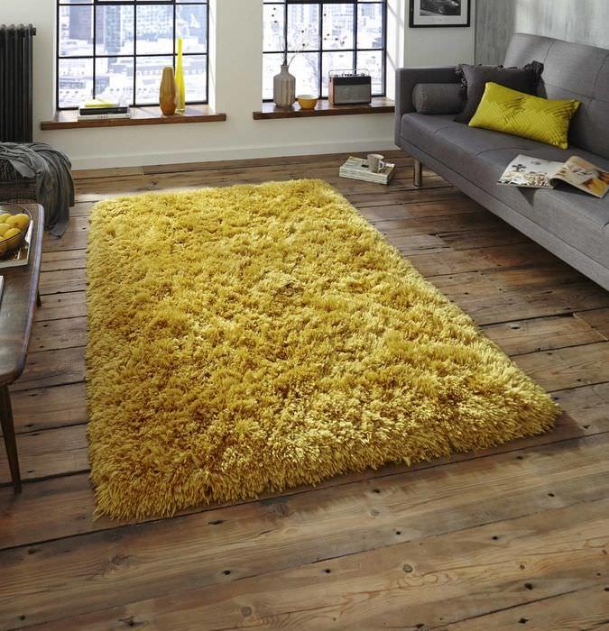 Желтый коврик на деревянном полу в темной спальне