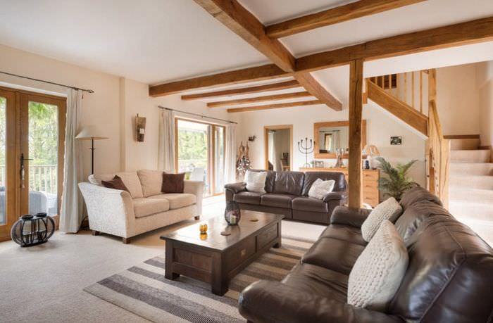 Деревянные балки на потолке гостиной с коричневым диваном