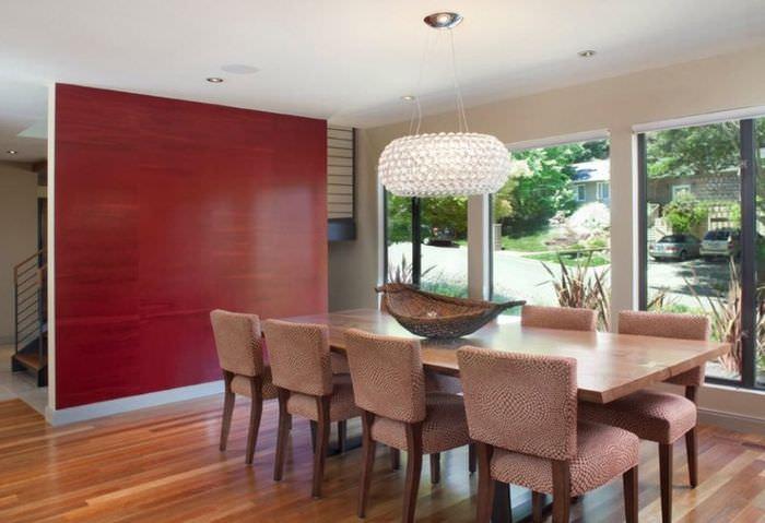 Удачное сочетание красной стены с темно-бежевыми стульями в обеденной зоне