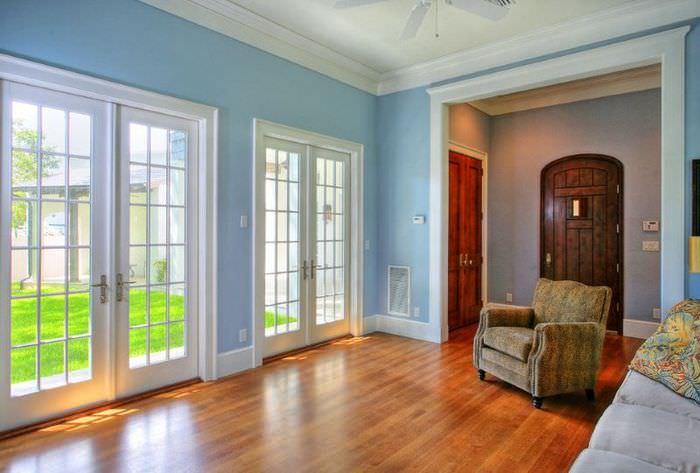 Белые входные двери в гостиной частного дома