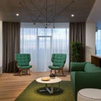 Зеленая мягкая мебель в серой гостиной