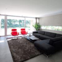 Красные стулья рядом с черным диваном