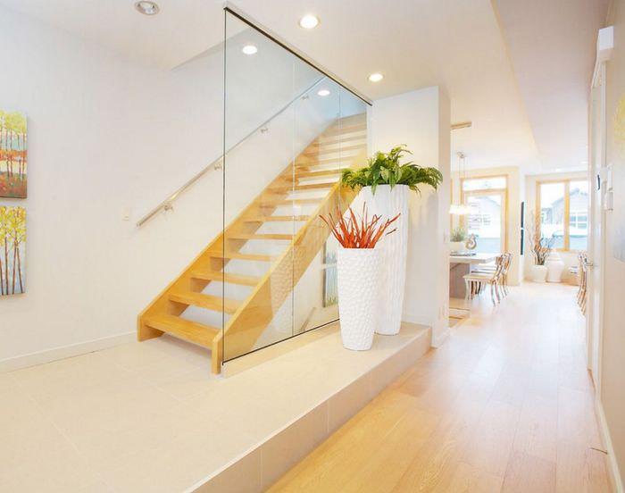 Две белые вазы с растениями в интерьере светлого холла загородного дома