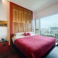 Красное покрывало на кровати в спальне многоэтажного дома