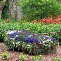 Оригинальная клумба с цветами из старой кровати