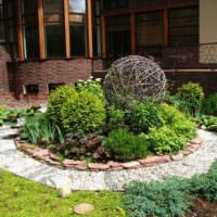 Шар из ивовых прутьев на клумбе садового участка