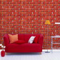 Красный диван на фоне кирпичной кладки