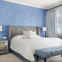 Голубые обои с цветами на стене спальной комнаты