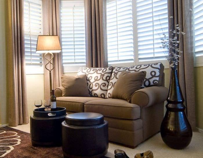 Напольная ваза черного цвета рядом с диваном в гостиной