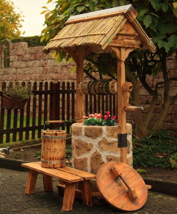 Малая архитектурная форма для сада в виде декоративного колодца из камня и дерева