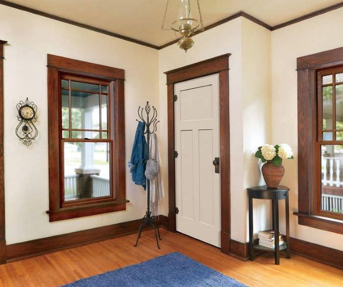 Коричневые наличники на проеме с белой дверью