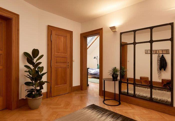 Прихожая частного дома с коричневым полом и деревянными дверями