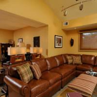 Коричневый диван на фоне желтых стен