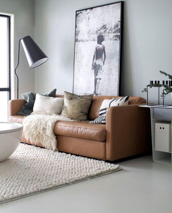 Интерьер гостиной с коричневым диваном на светло-сером покрытии пола