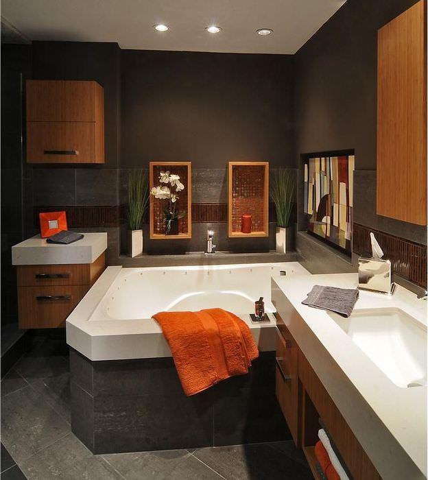 Оранжевое полотенце на краю ванны в темно-коричневой комнате