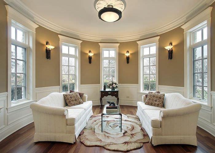 Интерьер гостиной частного дома в духе минимализма с люстрой по центру потолка