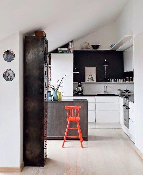 Интерьер кухни с наклонным потолком в мансардном помещении частного дома