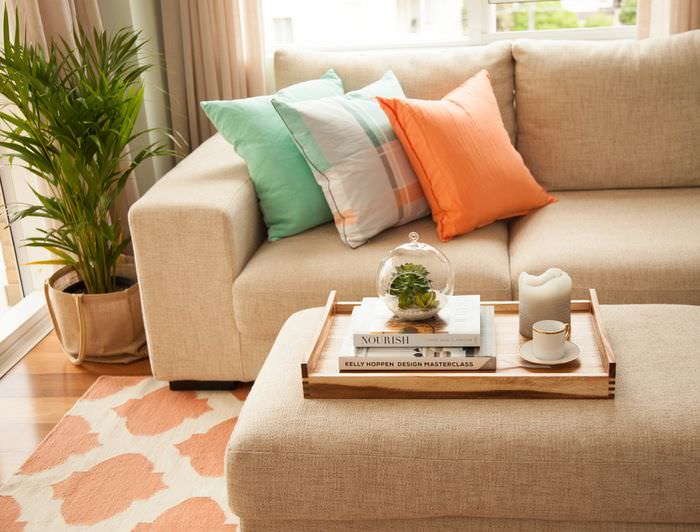 Оранжевая подушка на диване с обивкой из мешковины