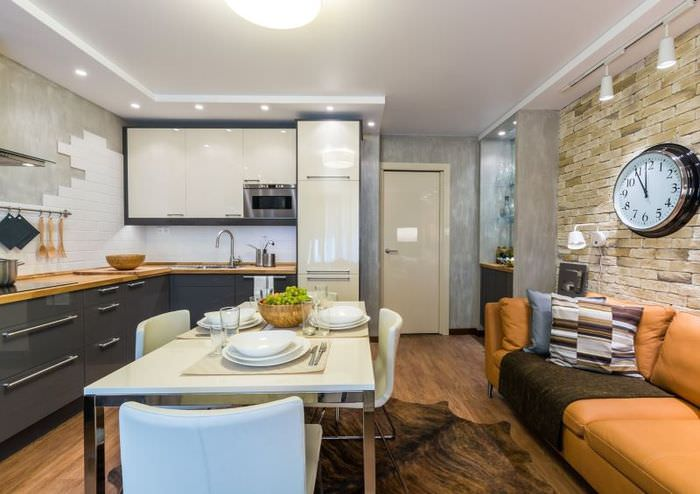 Оранжевый диван вдоль стены в кухне-гостиной с облицовкой из камня