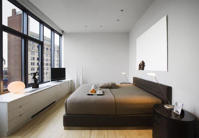 Панорамное остекление в светлой спальне с темной кроватью