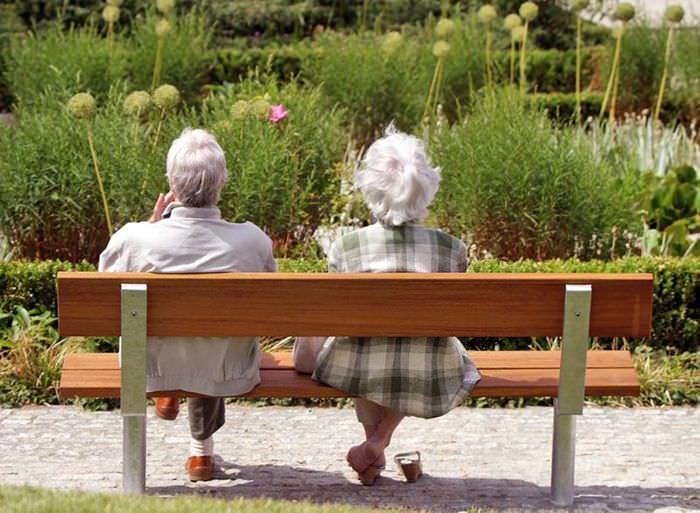 Пожилые люди отдыхают на деревянной скамейке в парке отдыха