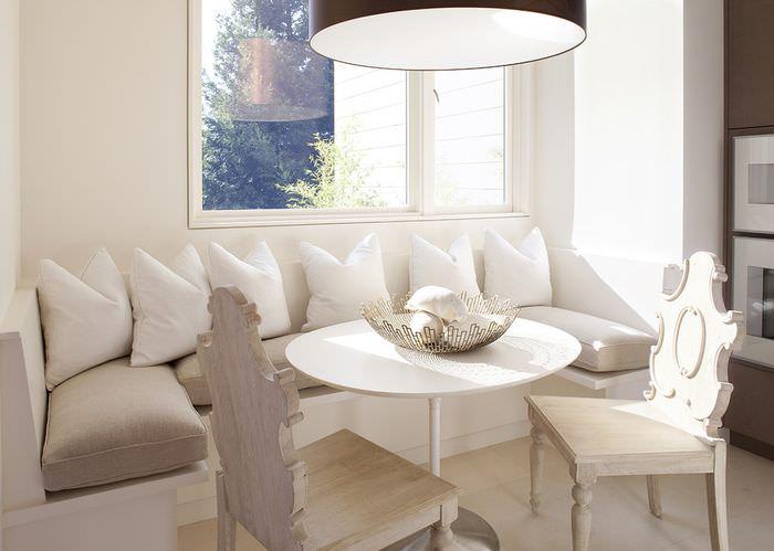 Белые подушки на диванчике в обеденной зоне