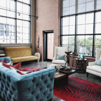 Голубой диван в гостиной с панорамными окнами
