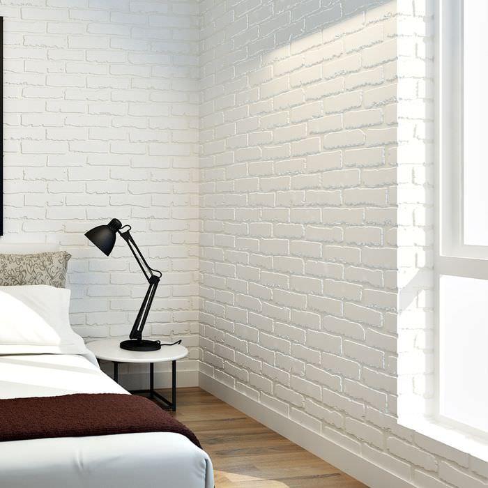 Черная настольная лампа на прикроватном столике в спальне с кирпичными обоями