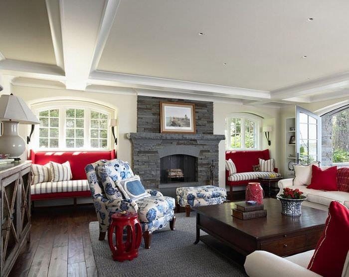 Сочетание красного, белого и голубого оттенков в интерьере гостиной с серым камином