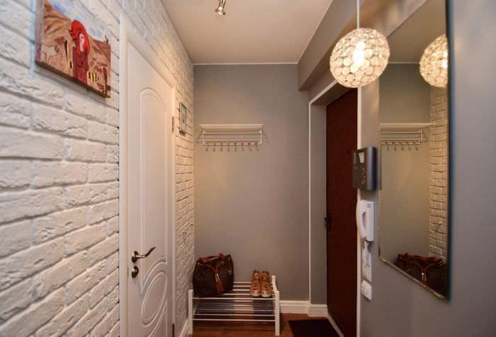 Белая стена из кирпича напротив зеркала в прихожей