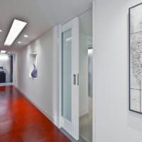 Сочетание красного пола с белой дверью в интерьере узкого коридора