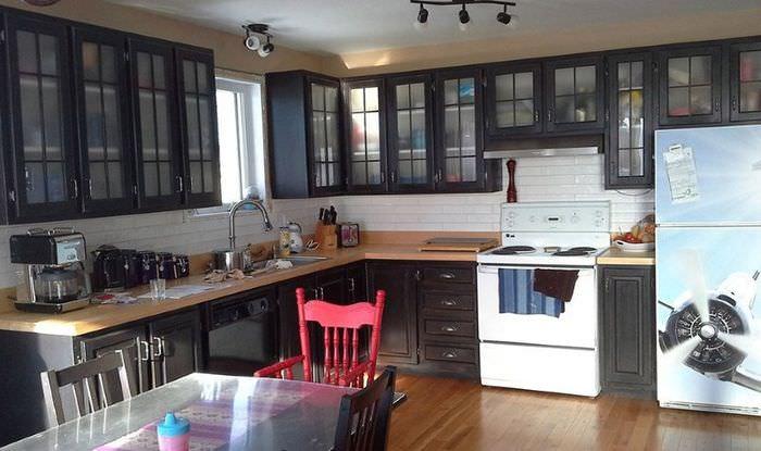 Кухонный гарнитур с темной отделкой и красный стул