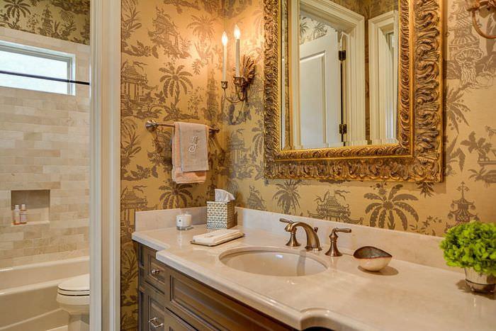 Белая раковина и зеркало в золотой рамке