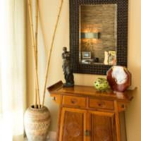Деревянный комод под настенным зеркалом