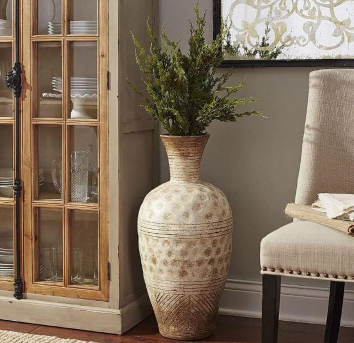 Классическая ваза с зелеными ветками на полу гостиной