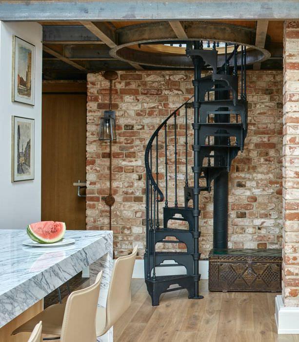 Винтовая лестница из черненного металла на второй этаж дома в стиле лофт
