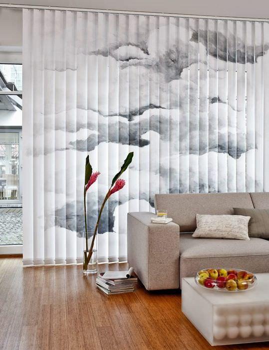 Серый диван на фоне вертикальных жалюзи