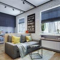 Серый диван на фоне белой кирпичной стены