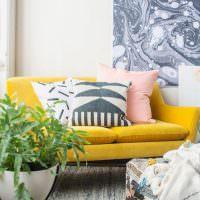 Серый коврик перед желтым диваном