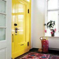 Пестрый ковер перед желтой дверью в прихожей
