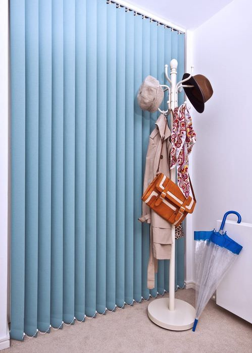 Вешалка для одежды около вертикальных жалюзи из ткани