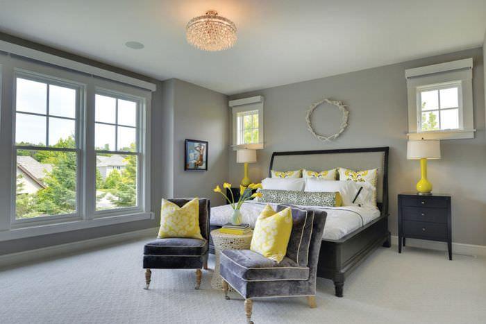 Желтые декоративные подушки в интерьере серой спальни