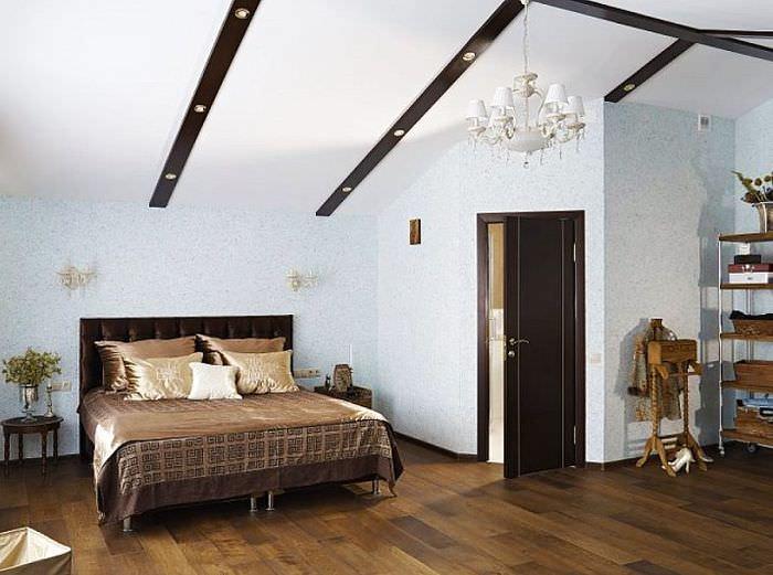 Светлые стены спальни в мансарде частного дома