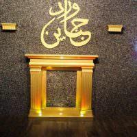 Декоративный камин с золотистой отделкой