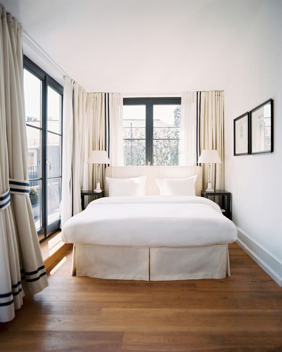 Белая кровать на коричневом полу из ламината