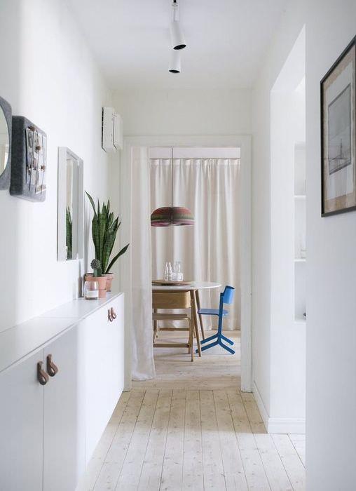 Светлый деревянный пол в прихожей с белыми стенами
