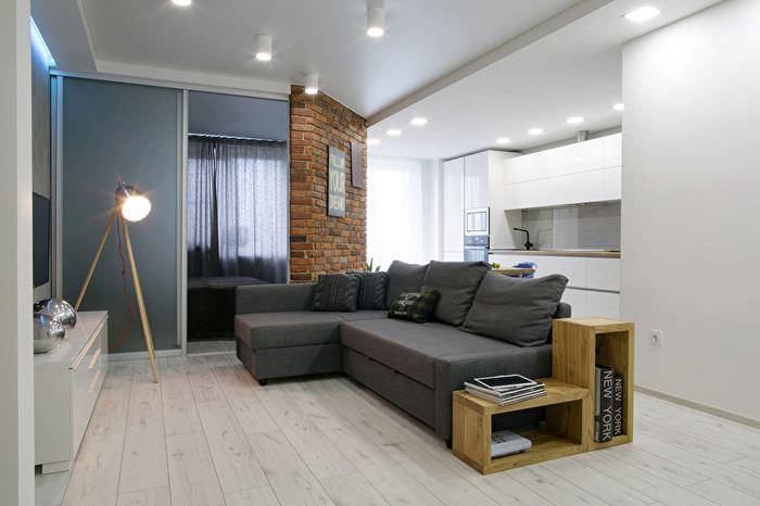 Белые стены в зале с темно-серым диваном