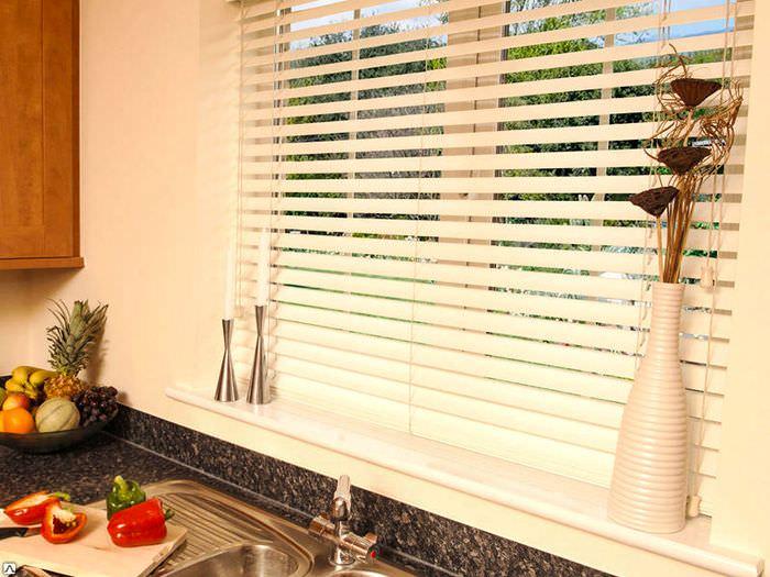 Белые жалюзи из пластика на окне кухни