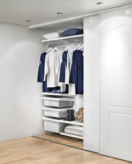Рубашки и кофты на вешалках внутри шкафа-купе