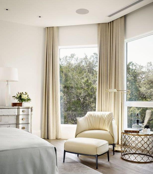 Высокие окна спальни с бежевыми шторами